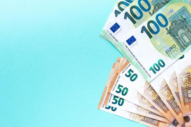 Il concetto di denaro e finanza. banconote da 100 e 50 euro disposte su uno sfondo blu sul lato destro. con posto per il testo. Foto Premium