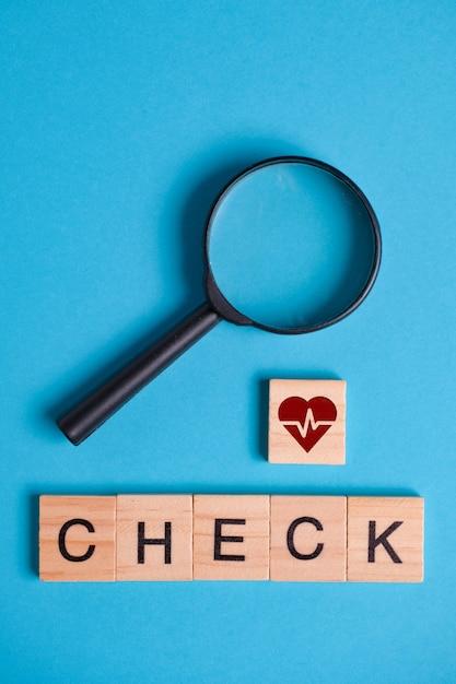 Il concetto di esame, controllo del cuore. il segno sulla piazza di legno accanto alla lente d'ingrandimento Foto Premium