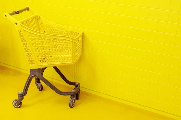 Il concetto di shopping. un carrello della spesa giallo vuoto si erge su un pavimento giallo Foto Premium