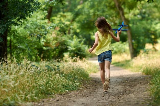 Il concetto di sogni e viaggi. bambino felice della ragazza che gioca con l'aeroplano del giocattolo di estate sulla natura. Foto Premium