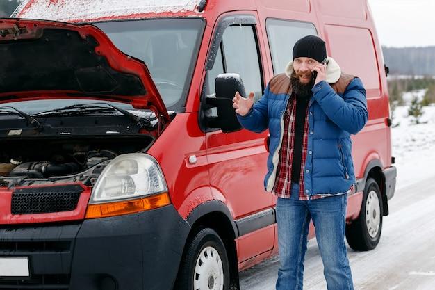 Il conducente chiama l'assistenza tecnica su strada in inverno. Foto Premium