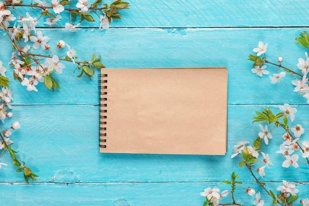 Il confine della primavera fiorisce la ciliegia che sboccia con il taccuino della carta in bianco sulla tavola di legno blu. vista dall'alto Foto Premium