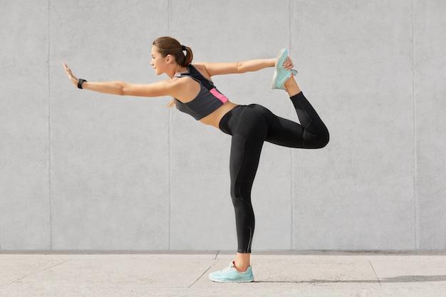 Il corridore femminile ha una bella figura, allunga le gambe prima della corsa, si riscalda, solleva la gamba, pratica yoga, indossa scarpe sportive Foto Gratuite