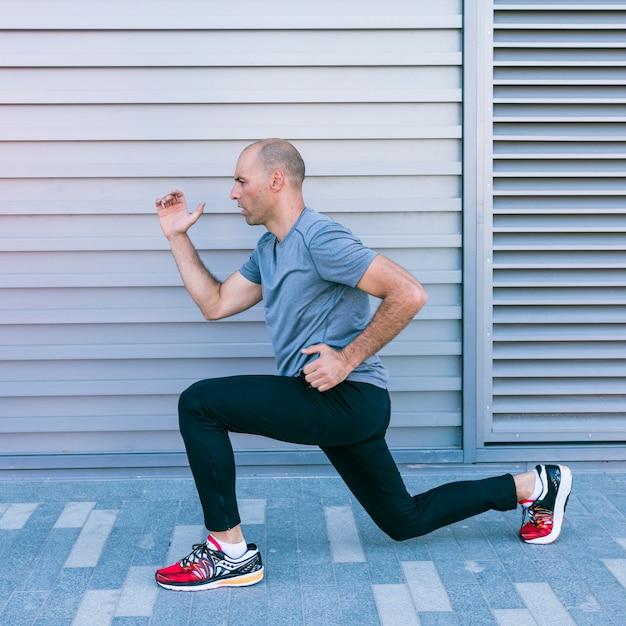 Il corridore maschio in buona salute che fa l'allungamento esercita prima ha cominciato la sua corsa Foto Gratuite