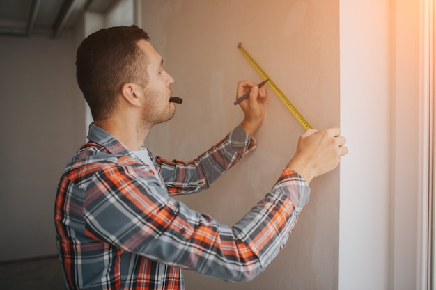 Il costruttore lavora al cantiere e misura la parete. il lavoratore in un casco arancione della costruzione fa le riparazioni nella casa Foto Premium