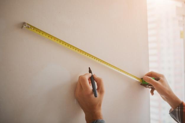 Il costruttore lavora in cantiere e misura il muro. il lavoratore in un casco arancione della costruzione fa le riparazioni nella casa Foto Premium