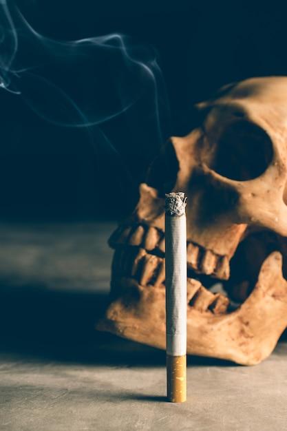 Il cranio astratto di natura morta di uno scheletro con la sigaretta bruciante, smette di fumare la campagna con copyspace. Foto Premium