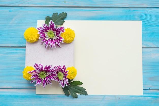 Il crisantemo fiorisce sopra la carta in bianco sulla tavola di legno blu Foto Gratuite