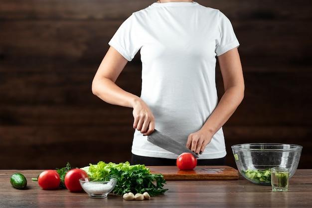 Il cuoco della donna taglia le verdure per la preparazione dell'insalata su legno. Foto Premium