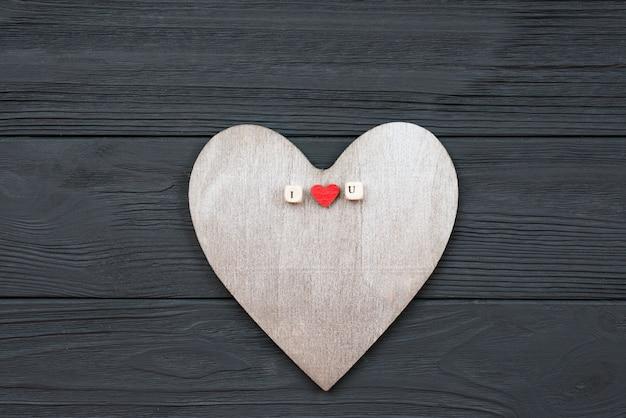 Il cuore di legno si trova su fondo di legno. concetto di eventi di amore, san valentino Foto Premium