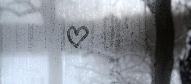 Il cuore è dipinto sul vetro appannato in inverno Foto Premium