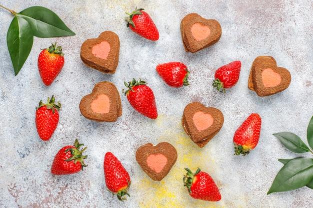 Il cuore ha modellato i biscotti con le fragole fresche, vista superiore della fragola e del cioccolato Foto Gratuite