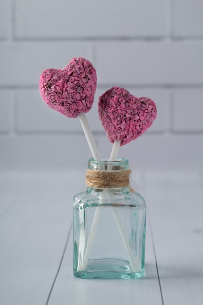 Il cuore ha modellato i morsi di energia per il san valentino in bottiglia sulla tavola di legno bianca Foto Premium