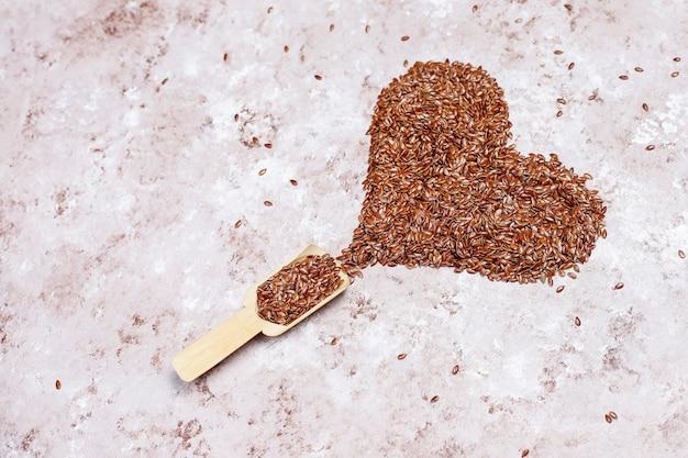 Il cuore ha modellato i semi di lino su fondo concreto con spazio per la copia, vista superiore Foto Gratuite
