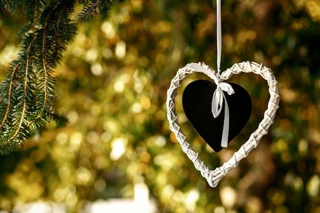 Il cuore nero messo nel cuore bianco pende dall'albero Foto Gratuite