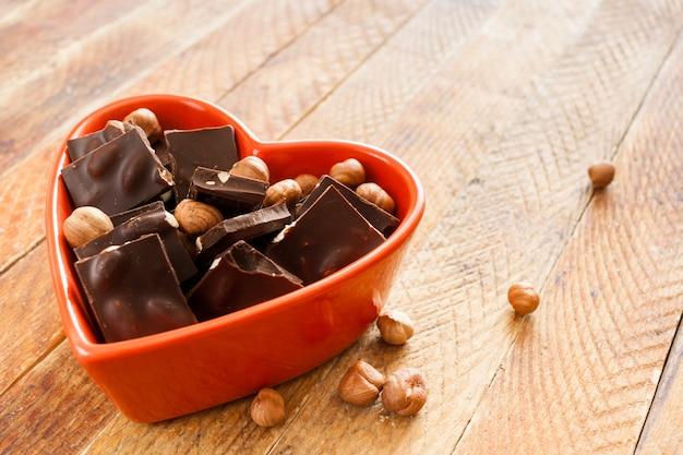 Il cuore rosso ha modellato la ciotola con i pezzi e le noci del cioccolato che si trovano diagonalmente sulla tavola di legno rustica. Foto Premium