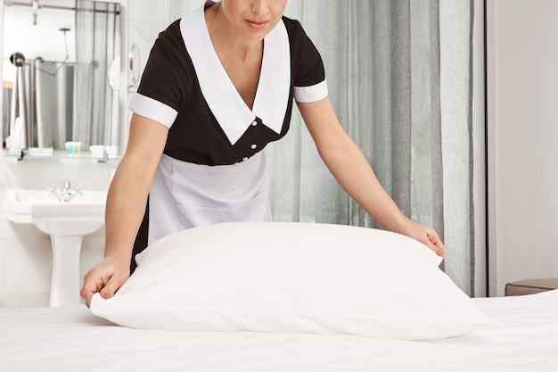 Il datore di lavoro sarà soddisfatto del risultato. ritagliata foto della cameriera che pulisce la camera da letto, rifà il letto e batte i cuscini per sembrare ordinata, riordinando la camera d'albergo prima che i nuovi visitatori si trasferiscano Foto Gratuite