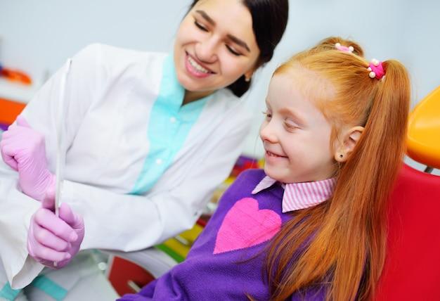 Il dentista dei bambini esamina i denti e la bocca del bambino - una ragazza carina dai capelli rossi seduta su una poltrona del dentista Foto Premium