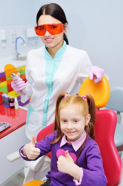 Il dentista della donna e la bambina del bambino una con capelli rossi nella sedia dentale le mostra i pollici Foto Premium