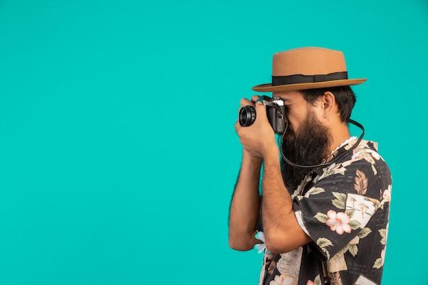Il di un turista maschio con una lunga barba che indossa un cappello e in possesso di una macchina fotografica su un blu. Foto Gratuite
