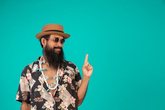 Il di un uomo felice con una lunga barba che indossa un cappello, indossa una camicia a righe che mostra un gesto su un blu. Foto Gratuite