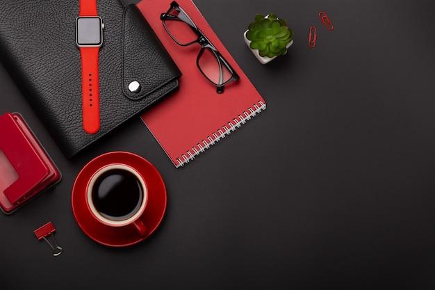 Il diario rosso del fiore della sveglia della tazza di caffè del fondo della tazza di caffè nero del fondo segna la tastiera sulla tavola. vista dall'alto con lo spazio della copia Foto Premium