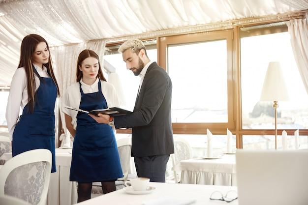 Il direttore di un ristorante sta dando istruzioni di lavoro alle cameriere Foto Gratuite
