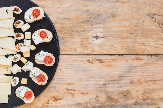 Il dispositivo d'avviamento saporito del formaggio con pane sull'ardesia nera imbarca sullo scrittorio di legno Foto Gratuite