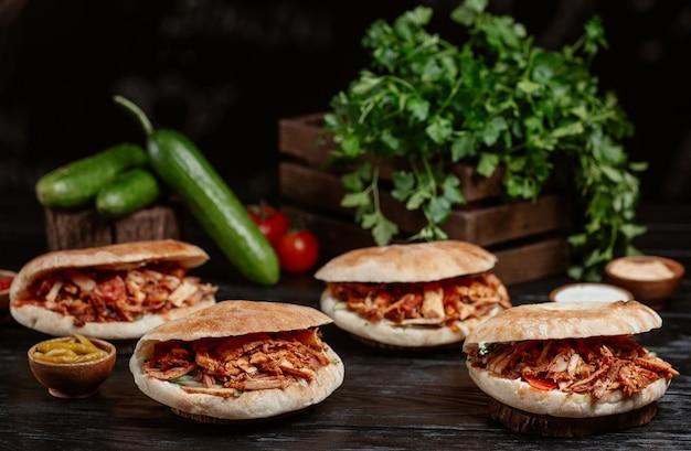 Il doner turco è servito dentro i panini di pane su una tavola di legno rustica Foto Gratuite