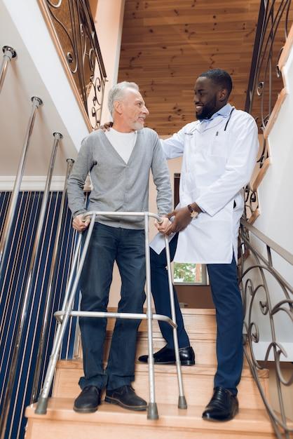 Il dottore aiuta un uomo a scendere le scale in una casa di riposo Foto Premium