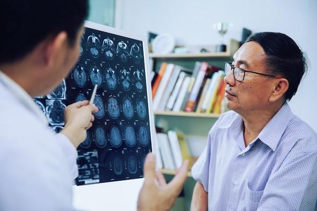 Il dottore dà consigli al paziente anziano sulle scansioni del cervello di mri (xray) Foto Premium