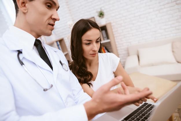 Il dottore sta mostrando qualcosa sul portatile a una ragazza incinta. Foto Premium