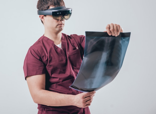 Il dottore usa occhiali per la realtà aumentata per esaminare i raggi x con lo scheletro umano Foto Premium