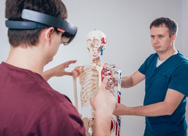 Il dottore usa occhiali per realtà aumentata e scheletro umano per insegnare agli studenti Foto Premium