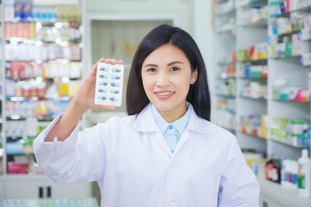 Il farmacista tiene un pacchetto di pillole nelle sue mani. Foto Premium