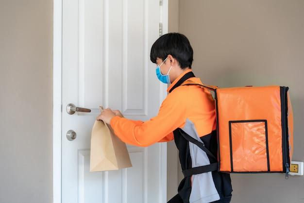 Il fattorino asiatico invia un sacchetto di cibo alla maniglia della porta per contatto senza contatto o senza contatto dal cavaliere di consegna nella casa di fronte per il social distanza per il rischio di infezione. concetto di coronavirus Foto Premium