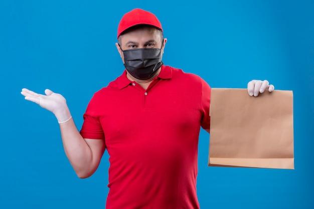 Il fattorino che indossa l'uniforme e il cappuccio rossi in maschera protettiva facciale che tiene il pacchetto di carta che presenta con il braccio oh consegna la parete blu Foto Gratuite