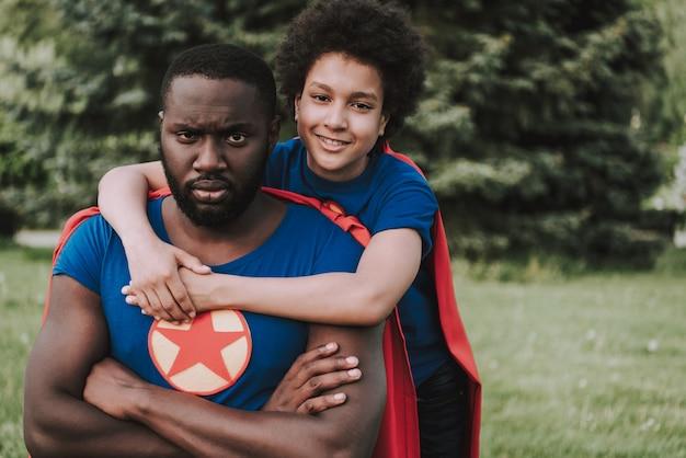 Il figlio in completo di supereroe abbraccia il padre serio Foto Premium