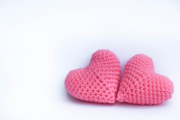Il filato per maglieria lavora all'uncinetto i cuori modellano il modello sveglio fatto a mano di colore rosa sul fondo dell'isolato Foto Premium