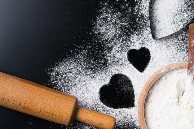 Il fondo di cottura con farina, il matterello e il cuore modellano su una tavola scura con lo spazio della copia, vista superiore, disposizione piana. concetto di cucina di san valentino Foto Premium
