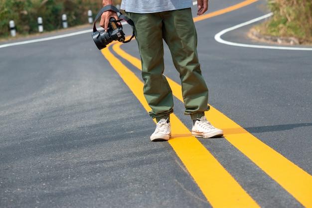 Il fotografo tiene in mano la macchina fotografica e cammina sulla strada Foto Premium