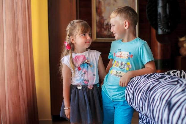 Il fratellino e sua sorella sono in piedi davanti alla finestra. Foto Premium