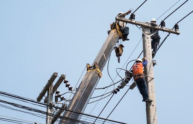 Il fuoco selettivo degli elettricisti sta riparando la linea di trasmissione di energia su un palo dell'elettricità Foto Gratuite