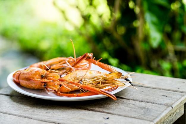 Il gamberetto arrostito ha messo i gamberetti sul piatto bianco, fine sulla tavola di legno messa grigliata dei frutti di mare Foto Premium