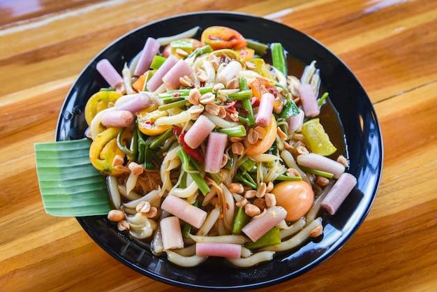 Il gambo del loto sull'insalata della papaia mescola la verdura e l'arachide della tagliatella servite sulle tagliatelle di riso del tavolo da pranzo Foto Premium