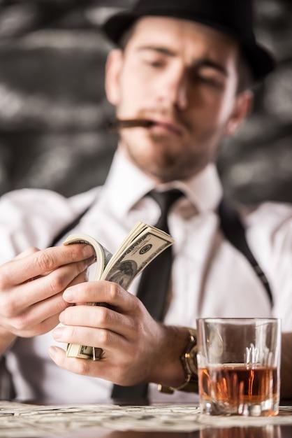 Il gangster in camicia e bretelle conta i soldi. Foto Premium
