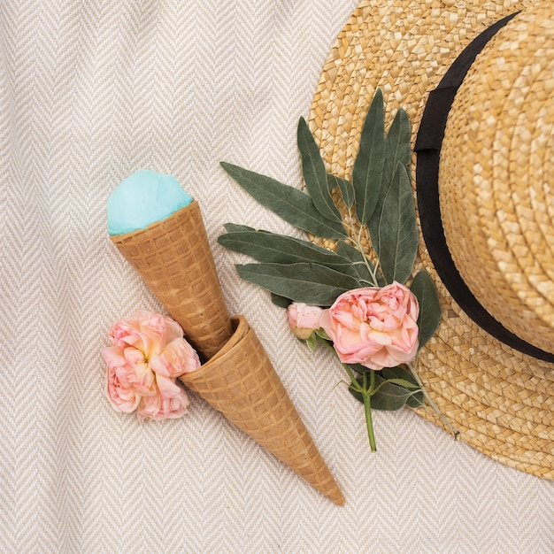 Il gelato blu in una cialda a cono si trova vicino a un cappello di paglia Foto Premium