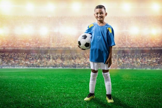 Il giocatore asiatico dei bambini di calcio nella condizione della jersey blu e posa alla macchina fotografica nello stadio Foto Premium
