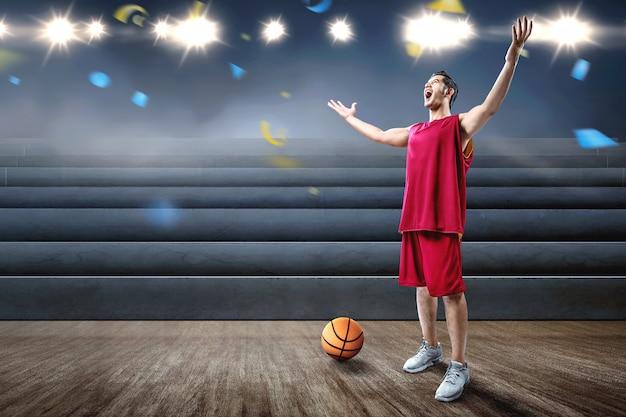 Il giocatore di pallacanestro asiatico dell'uomo celebra la vittoria Foto Premium