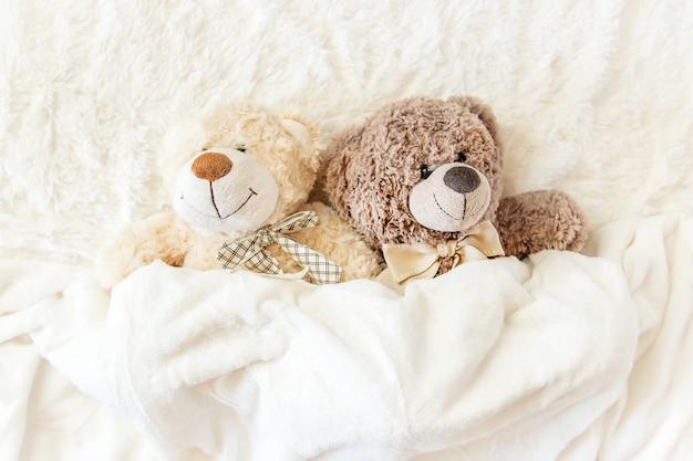 Il giocattolo per bambini dorme sotto la coperta. copia spazio. messa a fuoco selettiva Foto Premium